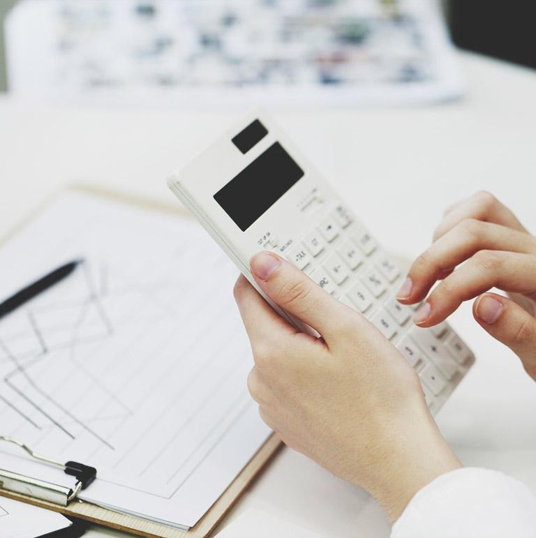 Osoba trzymająca kalkulator przy biurku